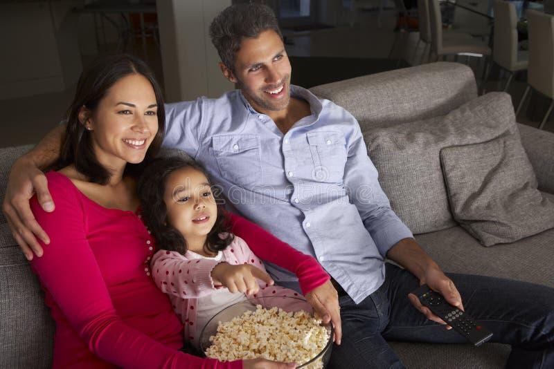 Latinamerikanskt flickasammanträde på Sofa And Watching TV med föräldrar arkivbild