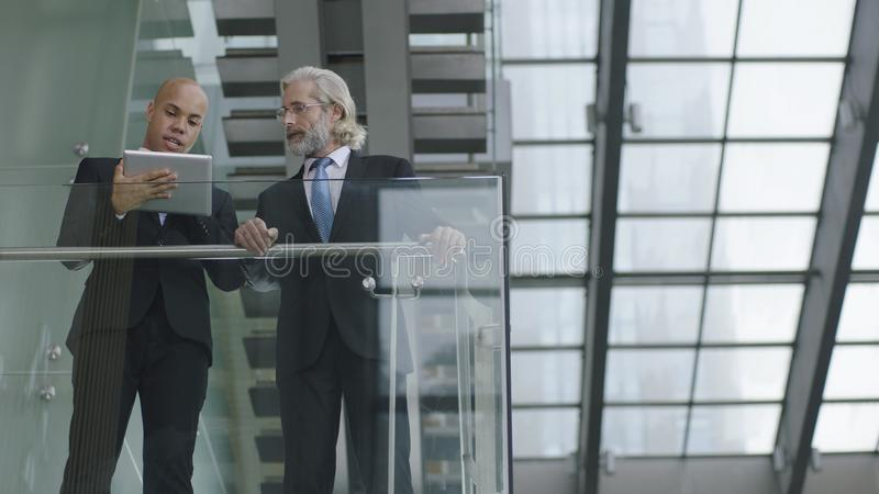 Two corporate executives standing and talking in modern office b stock image