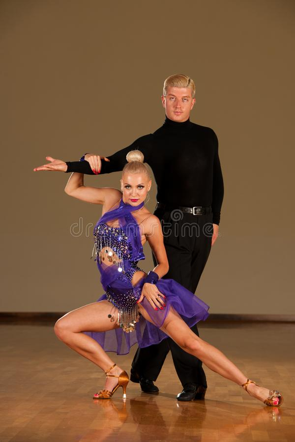 Latino dance couple in action preforming a exhibition dance - w. Ild samba stock photography