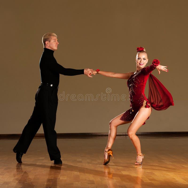 Latino danspaar die in actie een tentoonstellingsdans voorvormen - w royalty-vrije stock afbeeldingen