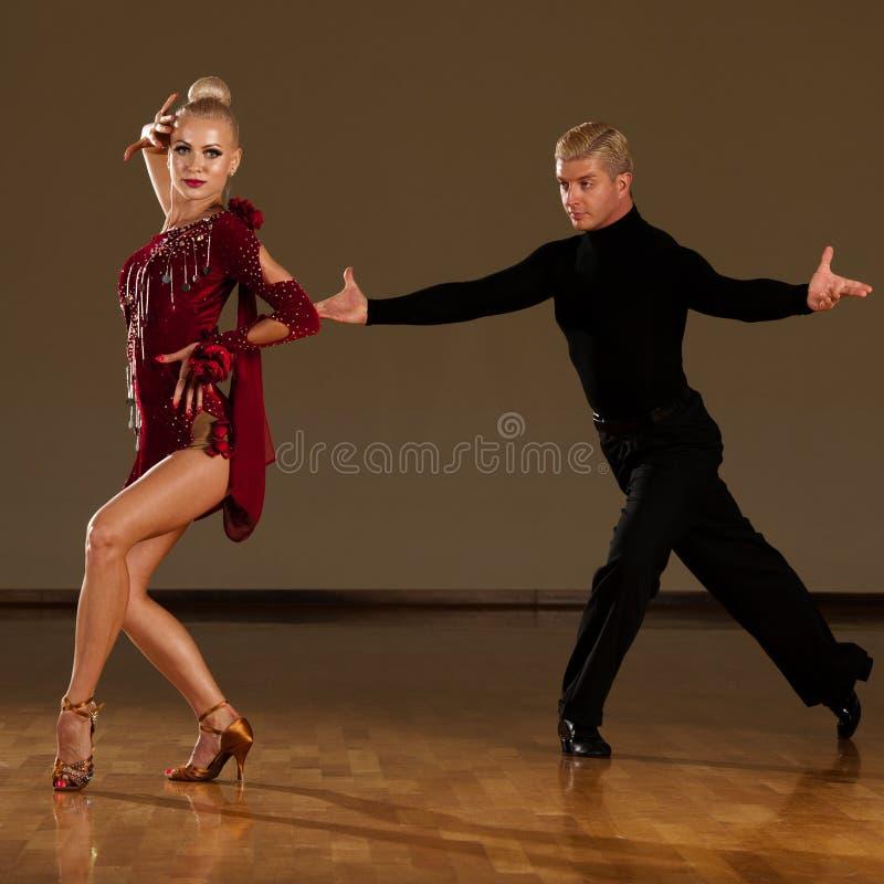 Latino danspaar die in actie een tentoonstellingsdans voorvormen - w stock fotografie