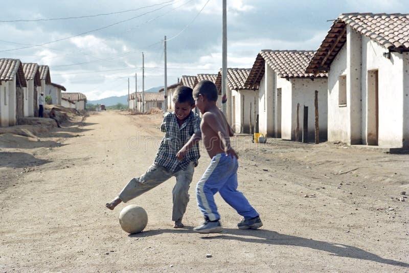 Latino jongens die voetbal in straat, Nicaragua spelen stock afbeeldingen