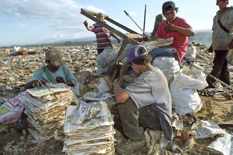 Latino jongens verzamelen oud document bij de stortplaats, Nicaragua stock fotografie