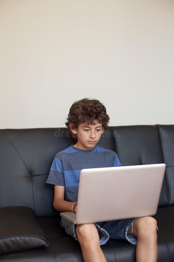 Latino jongenszitting op bank met laptop computer stock fotografie