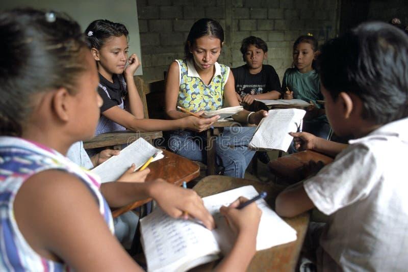 Latino leraar neemt een dichte blik aan schooltaken stock afbeeldingen