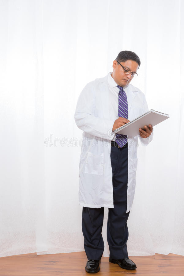 Latino Male Wearing Lab Coat And Holding Clipboard royalty free stock photo