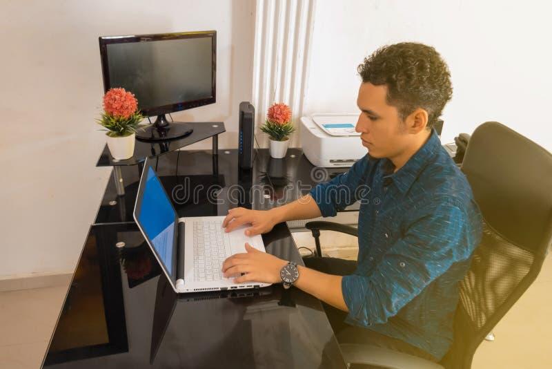 Latino-man som arbetar hemifrån på en bärbar dator Hemma, arbetar på distans i karantän royaltyfri bild