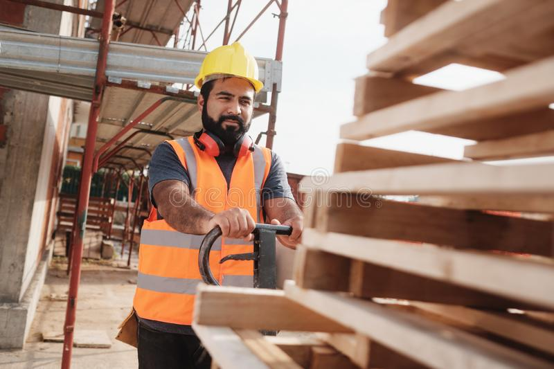 Latino Manual Worker With Forkift Pallet Stacker In Construction Site stock images