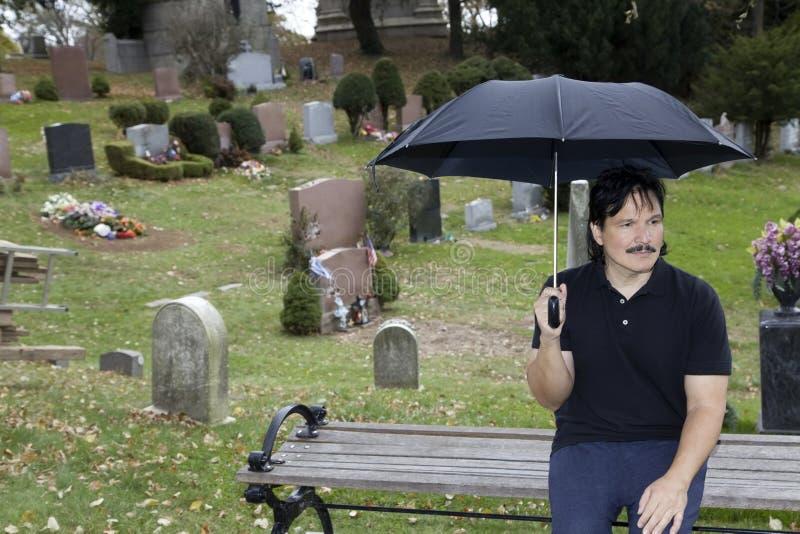 Latino mens zit met paraplu op bank in begraafplaats royalty-vrije stock fotografie