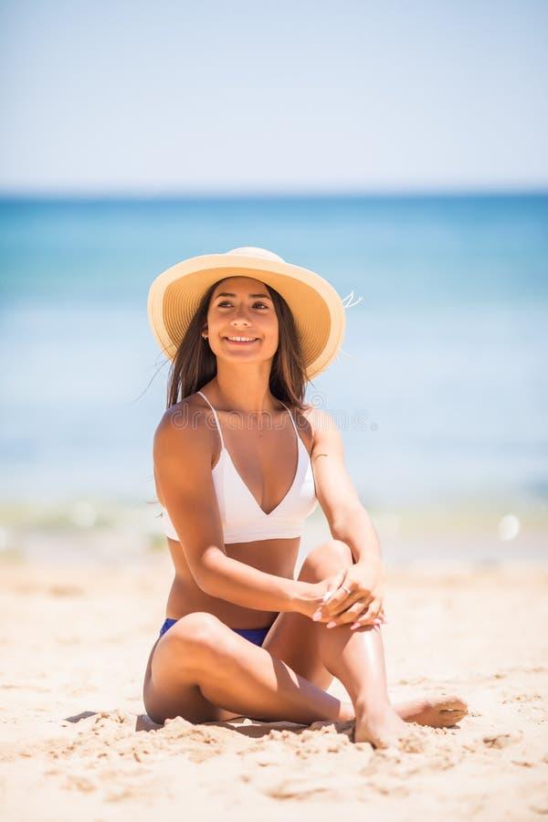 Latino novo atrativo no chapéu branco do biquini e de palha que levanta ao sentar-se na praia fotos de stock