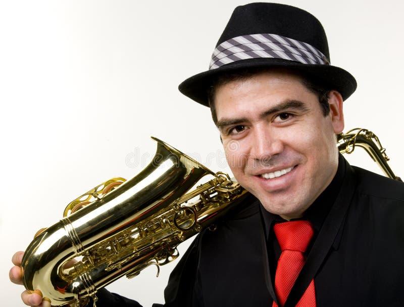 Latino Saxophone Player Isolated on White. A latino saxophone player with his instrument isolated on white royalty free stock photo
