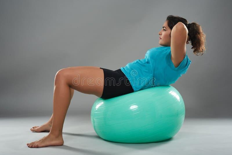 Latino vrouw die abs op gymnastiekbal doen stock foto's