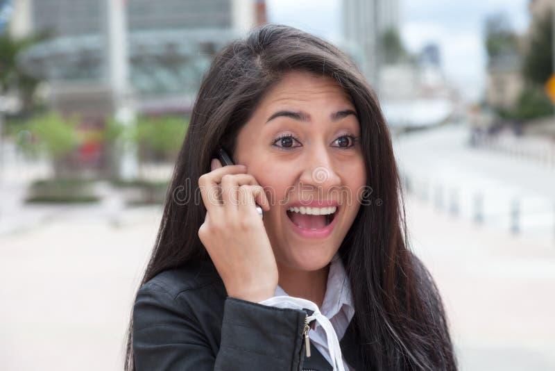 Latinsk kvinna för bifall som talar på telefonen i staden royaltyfria bilder