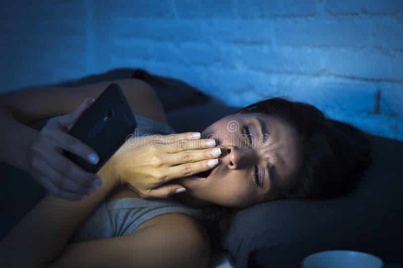 Latinsk kvinna på säng sent på natten som smsar genom att använda att gäspa för mobiltelefon som är sömnigt och som är trött arkivbild