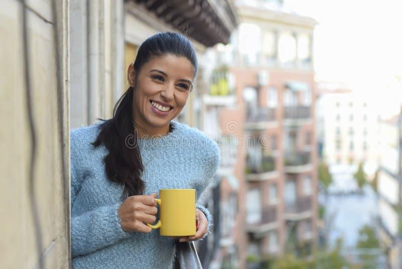 Latinsk kvinna som dricker att le för kopp kaffe som eller för te är lyckligt på lägenhetfönsterbalkongen royaltyfria foton