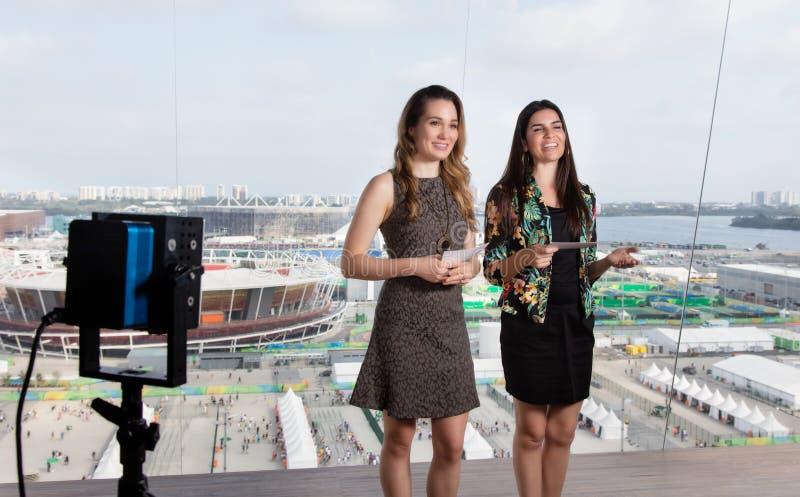 Latinsk kvinnlig presentatör och caucasian kvinna på tvstudion arkivfoton