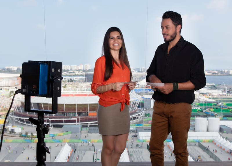Latinsk kvinnlig presentatör och caucasian man på tvstudion royaltyfri bild