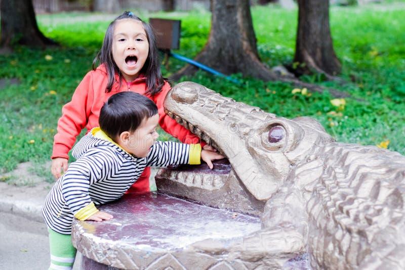 Latinsk liten sibling som är skrikig och trycker på tänderna av monumentet av en krokodil royaltyfri fotografi