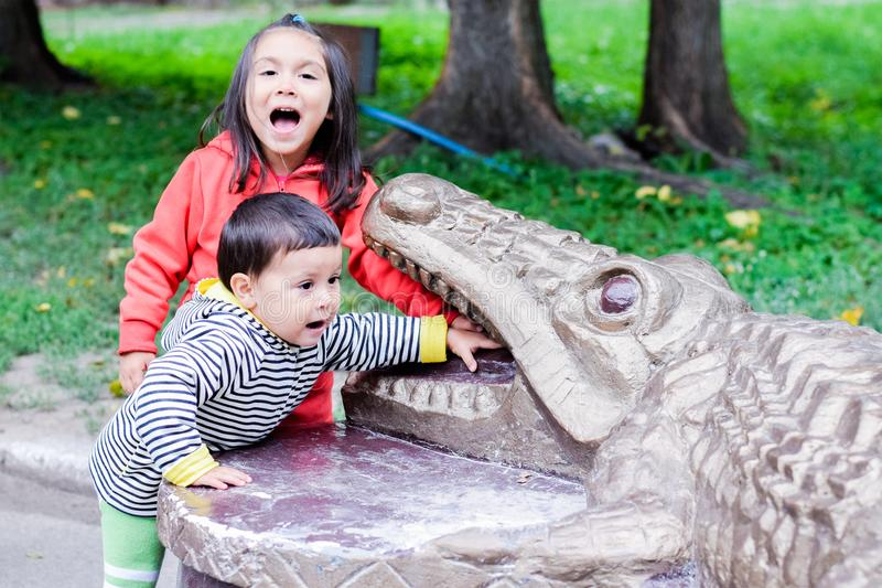 Latinsk liten sibling som är skrikig och trycker på tänderna av monumentet av en krokodil fotografering för bildbyråer