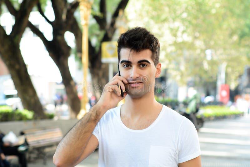 Latinsk man som talar p? telefonen royaltyfri bild