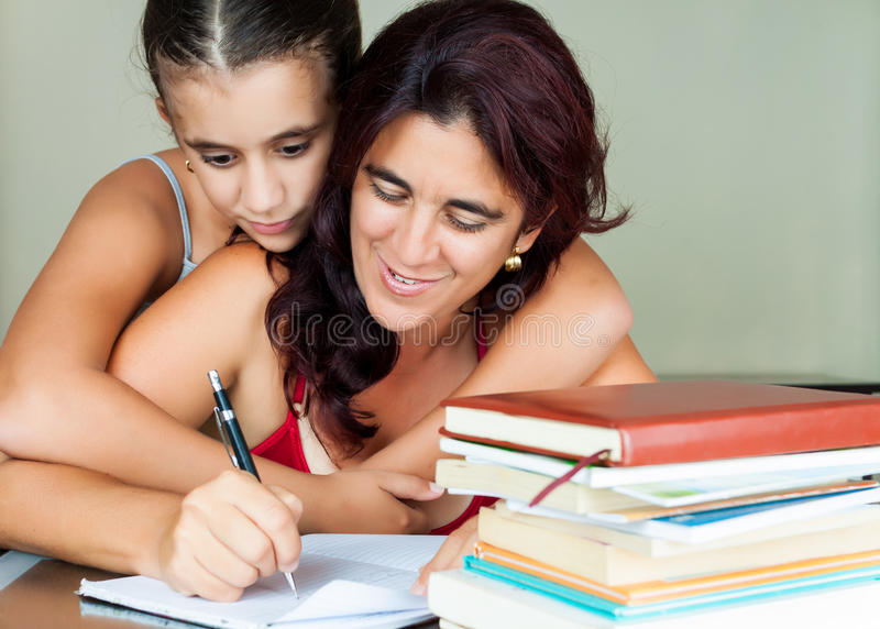 Latinsk moder och dotter som hemma studerar fotografering för bildbyråer