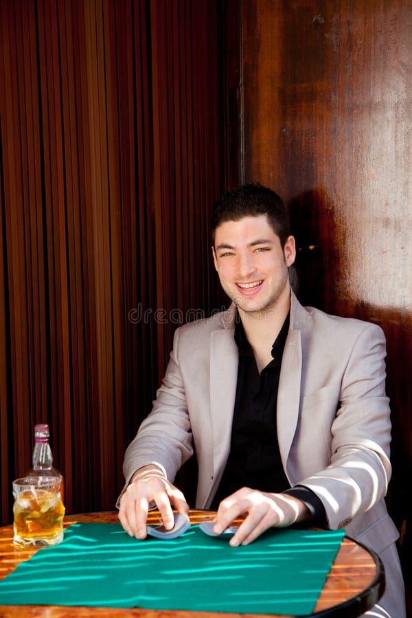 Latinsk stilig hasardspelareman i leka poker för tabell arkivfoto