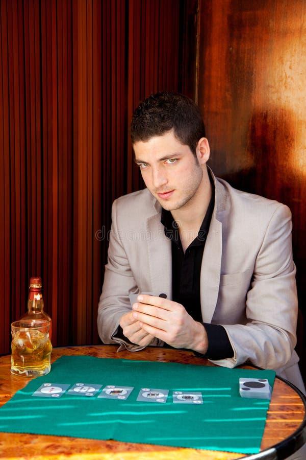 Latinsk stilig hasardspelareman i leka poker för tabell arkivbild