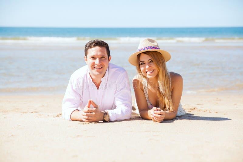 Latinska par som kopplar av på stranden royaltyfria bilder