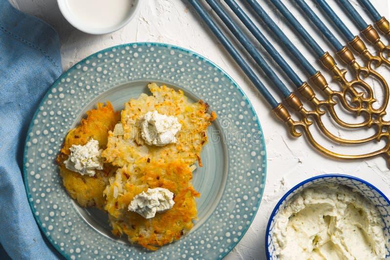 Latkes e ricotta su un piatto e su un tovagliolo blu, chanukia fotografie stock