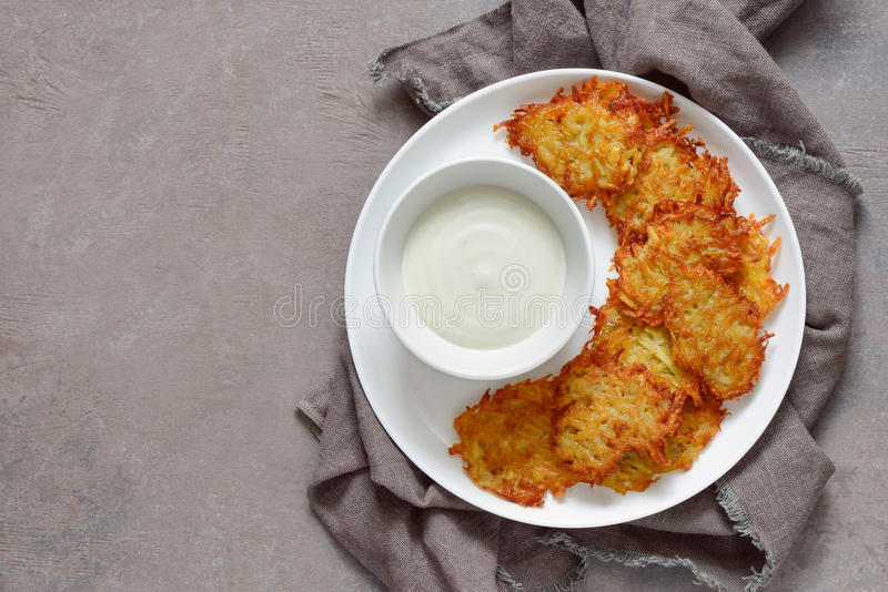 Latkes with sour cream. Latkes and sour cream in a plate, traditional hannukkah dish, view from above, space for a text royalty free stock image