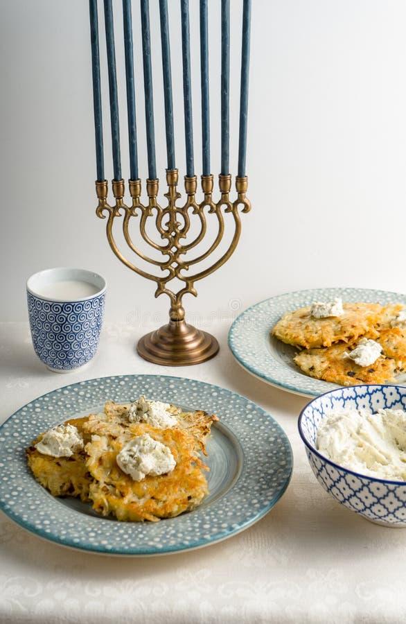 Latkes su un piatto, Chanukah, tazze con latte su una vista laterale della tovaglia bianca immagini stock