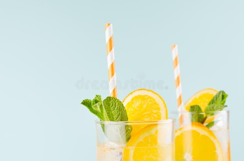 Lato świezi napoje z pomarańczami, kostka lodu, zieleni słomą w wineglass na błękit ścianie, nową i pasiastą, odgórna sekcja, kra obraz royalty free
