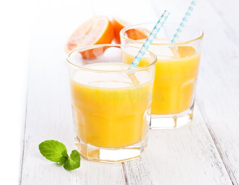 Lato żółta pomarańczowa lemoniada w szkle z krwionośnymi pomarańczami i słomą na drewnianym stole zdjęcia stock