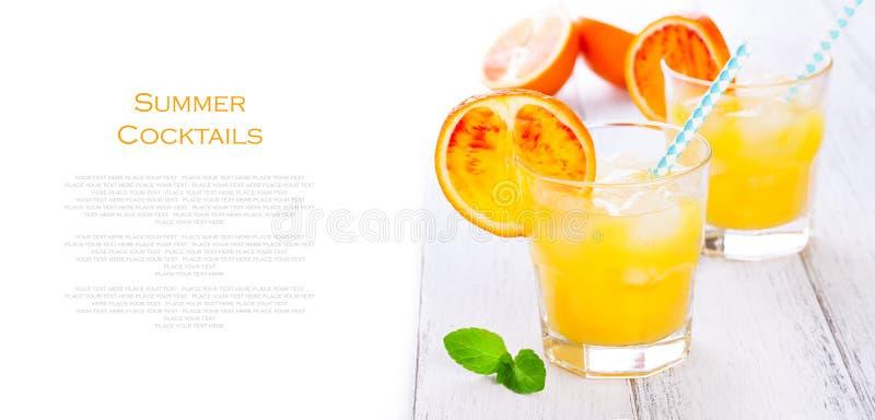 Lato żółta pomarańczowa lemoniada z lodem i pokojami krwionośne pomarańcze i słoma na drewnianym stole na białym tle z miejscem f obrazy stock