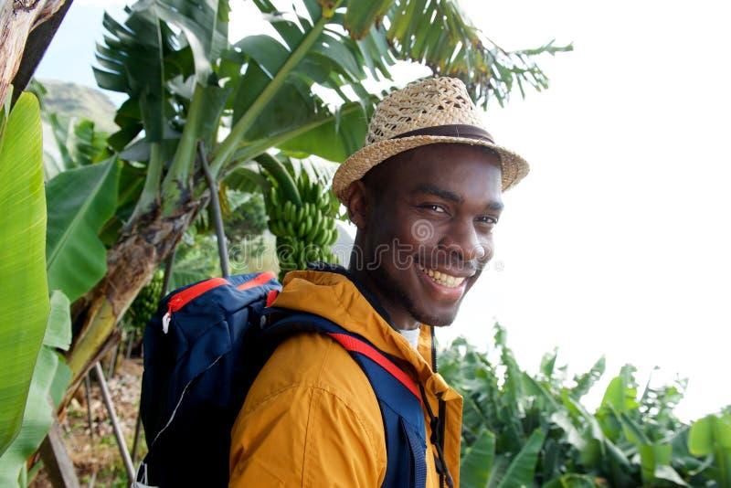 Lato alto vicino del viaggiatore maschio felice con la condizione dello zaino in natura fotografia stock libera da diritti