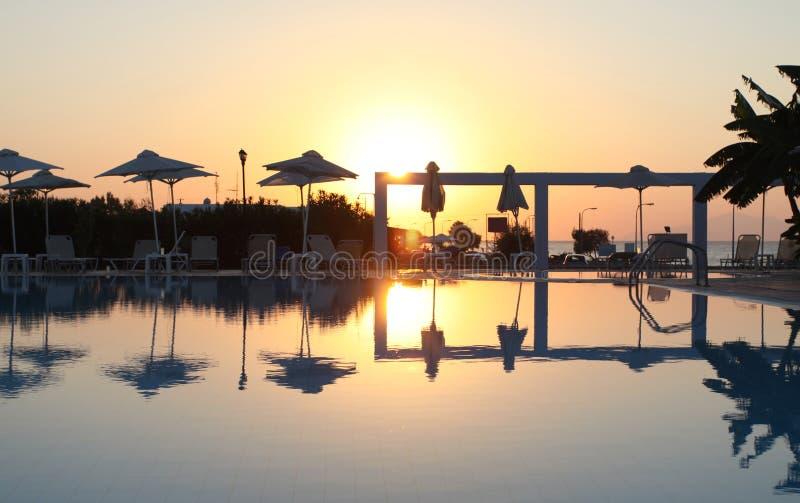 Lato czas: piękny widok zmierzch przy basenu terenem z palmą i parasols zdjęcie stock