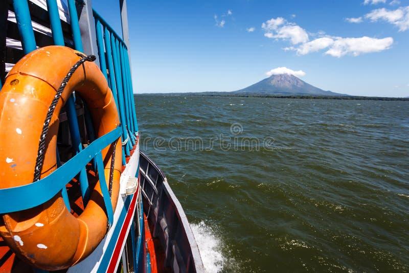 Lato del traghetto variopinto con l'anello arancio del conservatore di vita che accelera avanti nel lago al vulcano fotografia stock libera da diritti