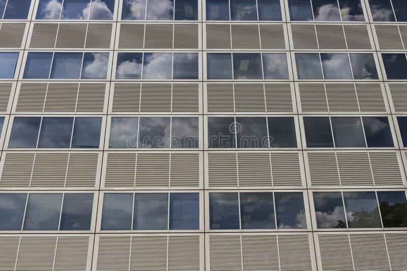 Lato di una costruzione del grattacielo con i pannelli grigi e finestre che riflettono il cielo con le nuvole I fotografie stock