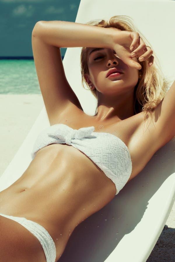 Lato dziewczyny model z garbnikującym seksownym ciałem Pozować w białym krześle na plaży tropikalna wyspa fotografia royalty free