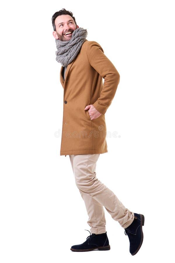 Lato integrale dell'uomo che cammina con il cappotto e la sciarpa contro il fondo bianco fotografia stock libera da diritti