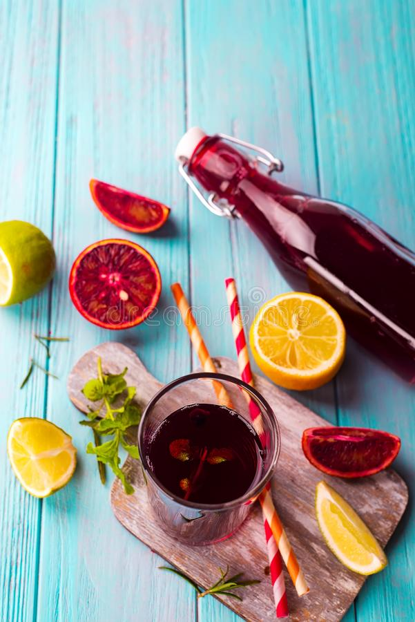 Lato jagodowy sok w szklanej butelce z cytrusem na błękitnym drewnianym tle zdjęcie stock