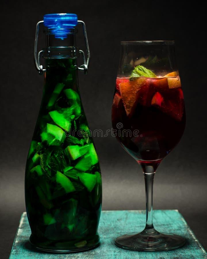 Lato jaskrawy - zielony czerwony owocowy koktajl w szkle, lemoniada, studio fotografia stock