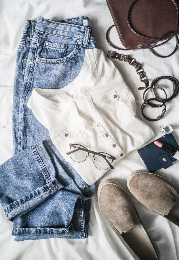 Lato kobiet mody ubrania ustawiają - mama cajgi, zamszowy sneakers, bawełniana koszulka, rzemienna torba, bransoletki, pomadka na zdjęcia royalty free
