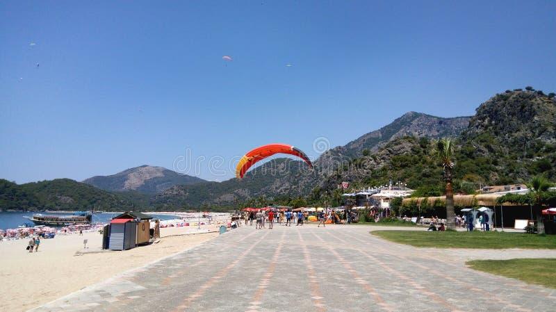 Lato krajobraz z górami, morzem, plażą, parasolem, drzewkami palmowymi i paragliding spada na nadmorski bulwarze, fotografia stock