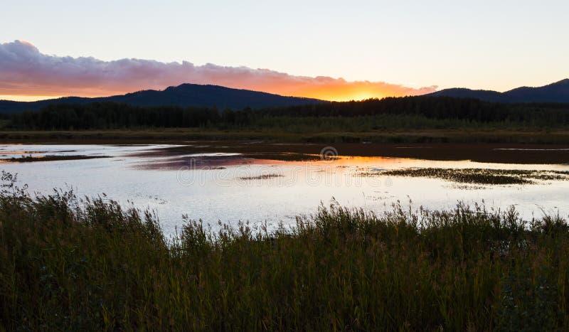 Lato krajobraz z rzecznym spływaniem między zielonymi wzgórzami na tle kolorowy zmierzchu niebo Ural region, Rosja obrazy stock