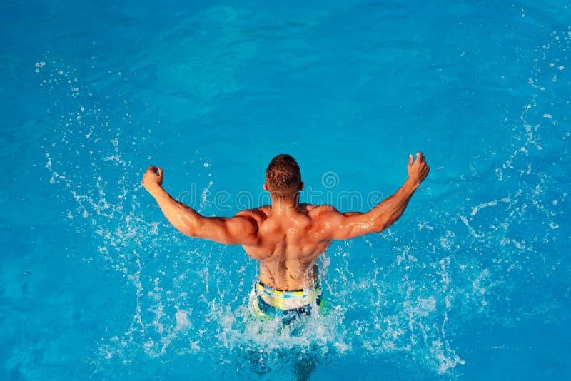 Lato m??czy?ni - z podnieceniem Luksusowy p?ywacki basen Relaksuje w zdroju p?ywackim basenie Przystojny m??czyzna ma zabaw? w le zdjęcia royalty free