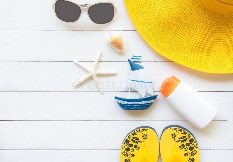 Lato mody kobiety żółty duży kapelusz i akcesoria w plaży tropikalne morza Niezwykły odgórny widok, drewniany biały tło obrazy stock