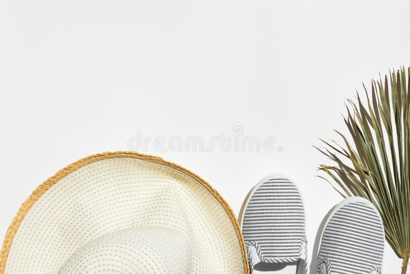 Lato mody podróży wakacje pojęcie Kobiety beachwear żeńska kapeluszowa kanwa paskujący buty suszą palmowego liść na białym tle obraz royalty free