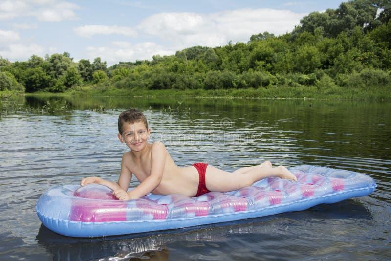 Lato na rzecznej chłopiec siedzi na nadmuchiwanej materac na ri fotografia stock