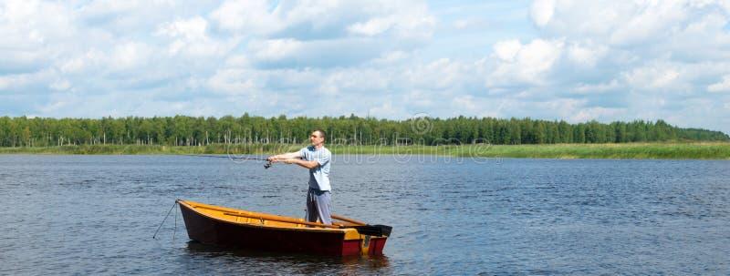 Lato na słonecznym dniu mężczyzna pozycja w łodzi na rzece łowi dla wirować obrazy royalty free